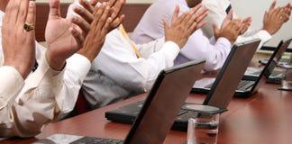 Hombres de negocios que aplauden sus manos en una reunión Imágenes de archivo libres de regalías