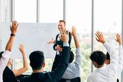 Hombres de negocios que aumentan para arriba su mano en acontecimiento con el altavoz en frente fotografía de archivo