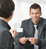 Hombres de negocios que cambian tarjetas Imágenes de archivo libres de regalías