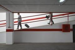 Hombres de negocios que caminan abajo de rampa con equipaje en parking Foto de archivo
