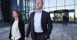 Hombres de negocios que caminan al aire libre almacen de metraje de vídeo