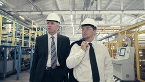 Hombres de negocios que caminan con fábrica y hablar almacen de video