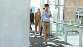 Hombres de negocios que caminan en el edificio de oficinas imagen de archivo