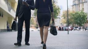 Hombres de negocios que caminan en la calle, comprobando el correo en smartphone, forma de vida ocupada metrajes