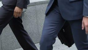 Hombres de negocios que caminan en las escaleras, funcionarios que comienzan día del trabajo, sociedad almacen de metraje de vídeo