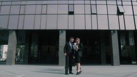 Hombres de negocios que caminan a través del pavimento delante del centro de negocios almacen de metraje de vídeo