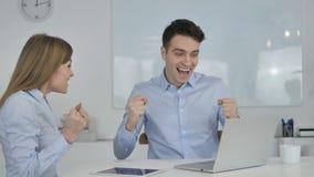 Hombres de negocios que celebran éxito mientras que trabaja en el ordenador portátil almacen de video