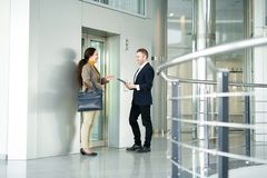 Hombres de negocios que charlan por el elevador imagen de archivo