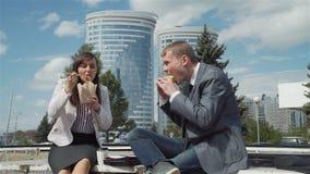 Hombres de negocios que comen y que charlan al aire libre metrajes