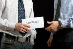 Hombres de negocios que comparten un contrato Foto de archivo