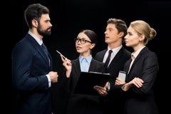 Hombres de negocios que conectan y que se colocan en el estudio aislado en negro Imagen de archivo libre de regalías