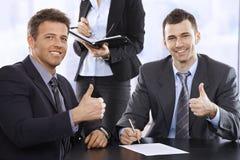 Hombres de negocios que dan los pulgares para arriba, sonriendo Fotos de archivo libres de regalías