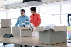 Hombres de negocios que desempaquetan pertenencia de la oficina de las cajas de cartón en la tabla fotografía de archivo