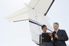 Hombres de negocios que discuten debajo de Wing Of Private Jet fotos de archivo libres de regalías