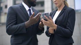 Hombres de negocios que discuten el inicio con los colegas vía el teléfono, conferencia en línea almacen de video
