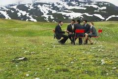 Hombres de negocios que discuten en campo de la montaña Imágenes de archivo libres de regalías
