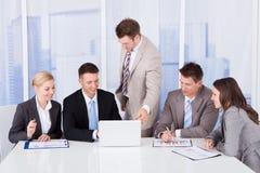 Hombres de negocios que discuten en el ordenador portátil en oficina Imagen de archivo libre de regalías