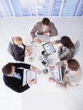 Hombres de negocios que discuten en gráficos en la mesa de reuniones Foto de archivo