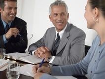 Hombres de negocios que discuten en la mesa de reuniones Imágenes de archivo libres de regalías
