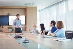 Hombres de negocios que discuten en la mesa de reuniones durante la reunión Imagen de archivo libre de regalías