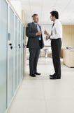 Hombres de negocios que discuten en pasillo de la oficina Foto de archivo libre de regalías
