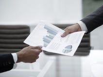 Hombres de negocios que discuten gráficos financieros Imagen de archivo