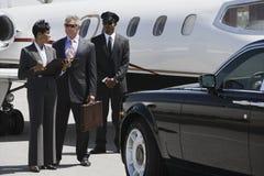 Hombres de negocios que discuten informes en el campo de aviación Imagen de archivo