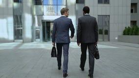 Hombres de negocios que discuten inicio mientras que se acerca al centro de la oficina, sociedad metrajes