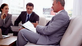 Hombres de negocios que discuten junto en un sofá