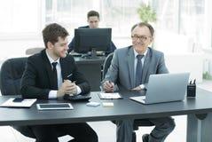 Hombres de negocios que discuten la acción del documento en la oficina Foto de archivo
