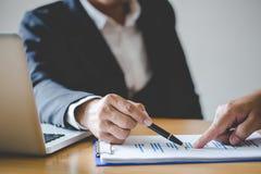 Hombres de negocios que discuten las cartas y los gráficos que muestran los resultados de su trabajo en equipo acertado, imagen d fotos de archivo libres de regalías