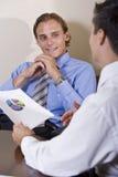 Hombres de negocios que discuten resultados financieros Foto de archivo