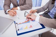 Hombres de negocios que discuten sobre gráfico en oficina Fotografía de archivo libre de regalías