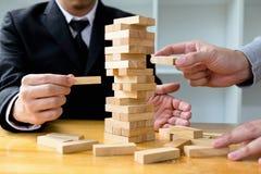 Hombres de negocios que escogen bloques del dominoe para llenar los dominós que falta y para proteger dominó para fallar Concepto imagenes de archivo
