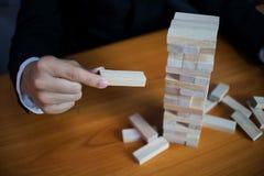 Hombres de negocios que escogen los bloques de madera para llenar los domin?s que falta Concepto cada vez mayor del asunto imagenes de archivo