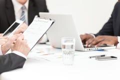 Hombres de negocios que escriben la nota en la reunión Imagen de archivo