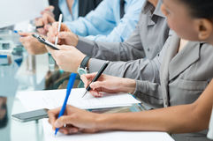 Hombres de negocios que escriben notas en la reunión Imágenes de archivo libres de regalías
