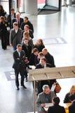 Hombres de negocios que esperan en la exposición y la feria profesional Foto de archivo libre de regalías