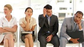 Hombres de negocios que esperan una entrevista en fila almacen de metraje de vídeo