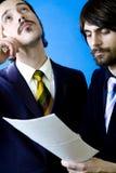 Hombres de negocios que estudian el contrato imágenes de archivo libres de regalías