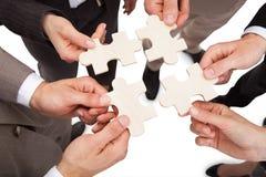 Hombres de negocios que fijan pedazos del rompecabezas Foto de archivo libre de regalías