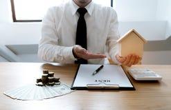 Hombres de negocios que firman el contrato que hace un trato con las propiedades inmobiliarias fotografía de archivo