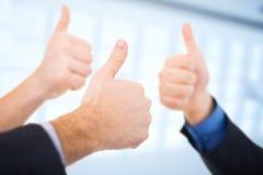 Hombres de negocios que gesticulan los pulgares para arriba Foto de archivo libre de regalías
