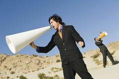 Hombres de negocios que gritan a través de los megáfonos en desierto fotografía de archivo libre de regalías