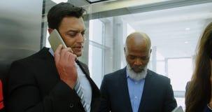 Hombres de negocios que hablan en el teléfono en el elevador 4k almacen de metraje de vídeo