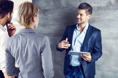 Hombres de negocios que hablan en la oficina usando la tableta Foto de archivo