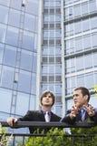 Hombres de negocios que hablan fuera del edificio imagen de archivo