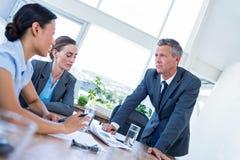 Hombres de negocios que hablan junto durante la reunión fotos de archivo libres de regalías
