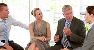 Hombres de negocios que hablan junto en oficina almacen de video