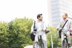Hombres de negocios que hablan mientras que el montar monta en bicicleta al aire libre Imagenes de archivo